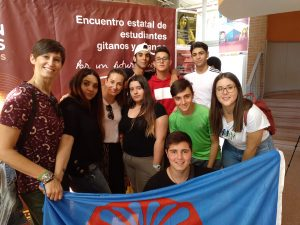 Grupo de estudiantes sosteniendo la bandera gitana